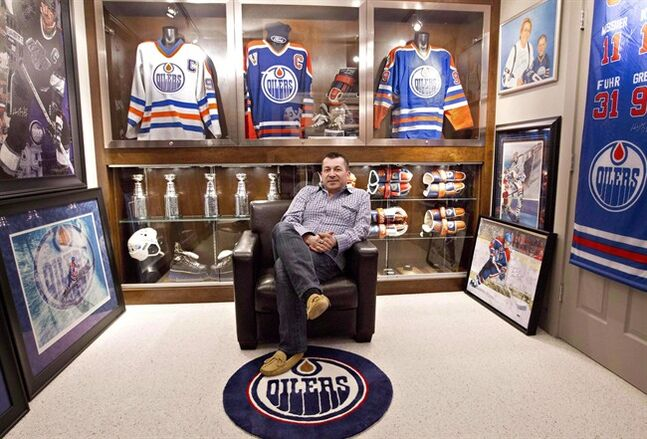 Shawn Chaulk poses with his collection of Wayne Gretzky memorabilia in Fort McMurray, Alta., on April 16, 2013. A hockey jersey that symbolizes the handover of greatness from one era to another is to go on the block this week at a Montreal auction. A sports lover some call the Wayne Gretzky of Wayne Gretzky collectors has decided to sell the jersey worn by the Great One during his entire breakout season. THE CANADIAN PRESS/Jason Franson