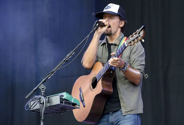 "FILE - This Aug. 18, 2013 file photo shows U.S singer Jason Mraz performing at the V Festival in Chelmsford, England. Mraz announced Wednesday, July 16, 2014, he would tour the five boroughs of New York in September. Mraz said at a conference at the Empire State Building that he would kick it off Sept. 17 at the Brooklyn Center for Performing Arts at Brooklyn College. ""The Five Boroughs Tour"" will wrap with two nights at Manhattan's Radio City Music Hall on Sept. 22 and 23. Tickets for all shows go on sale July 21. (Photo by Jonathan Short/Invision/AP, File)"