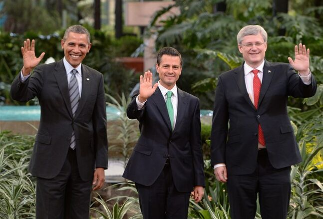 Canadian Prime Minister Stephen Harper (right to left) Mexican President Enrique Pena Nieto and U.S. President Barack Obama wave during a photo opportunity at the North American Leaders Summit in Toluca, Mexico on Wednesday, Feb.19, 2014. THE CANADIAN PRESS/Sean Kilpatrick