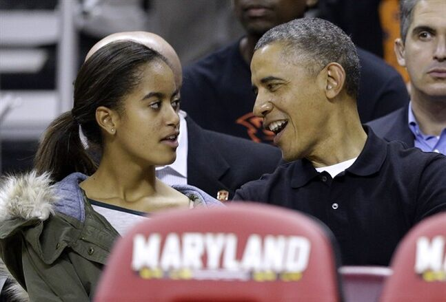 FILE - This Nov. 17, 2013, file photo shows President Barack Obama as he chats with daughter Malia before an NCAA college basketball game between Maryland and Oregon State in College Park, Md. President Obama is practically weepy at the thought of his daughter Malia going off to college, a milestone many months away that is on his mind now. At 16, she stands nearly as tall as her 6-foot-1 dad and is visiting college campuses in preparation for that bittersweet day in the fall of 2016 when she trades her White House bedroom for a dorm. (AP Photo/Patrick Semansky, File)