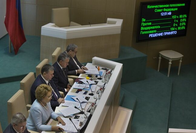 Speaker of Federation Council members Valentina Matviyenko, second left, looks at the screen in front of her during the voting in the Russian parliament's upper chamber in Moscow, Russia, Wednesday, June 25, 2014. On Russian President Vladimir Putin's demand, the upper house of Russian parliament on Wednesday canceled a resolution allowing the use of military in Ukraine, a move intended to show Moscow's eagerness to de-escalate tensions and avoid a new round of Western sanctions. (AP Photo/Alexander Zemlianichenko)
