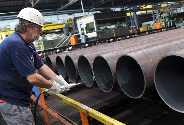 FILE - In this July 9, 2013 file picture an employee checks a steel pipe in the manufacturing hall at Vallourec and Mannesmann in Duesseldorf,�Germany. German industrial production declined significantly in May, a third consecutive drop that suggests slowing growth in China and tensions over Ukraine may be having an impact on Europe's biggest economy. The Federal Statistical Office said Monday July 7, 2014 that production was down 1.8 percent compared with the previous month. In April, it slipped 0.3 percent- revised downward from the initial reading of 0.2 percent growth. (AP Photo/dpa, Caroline Seidel,file)