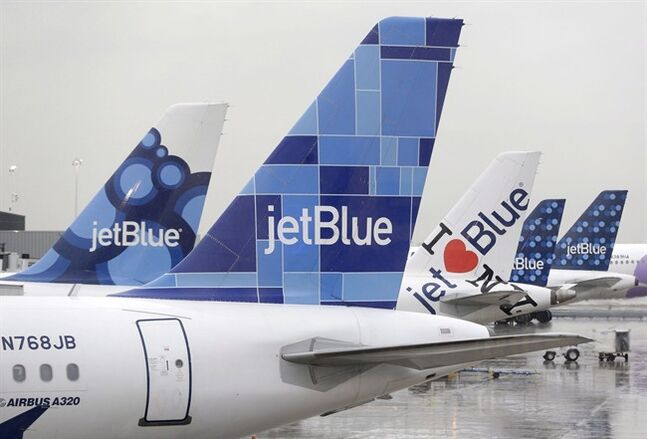 JetBlue airplanes at their gates at John F. Kennedy Airport in New York, Nov. 27, 2013. (AP Photo/Seth Wenig)