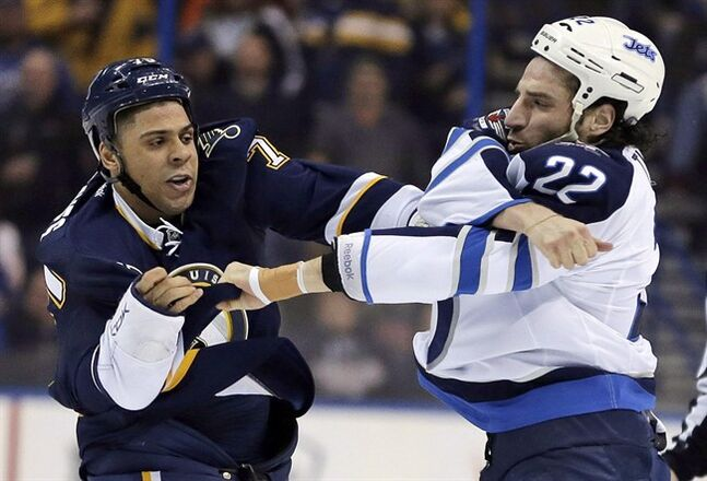 St. Louis Blues' Ryan Reaves, left, and Winnipeg Jets' Chris Thorburn fight during the first period of an NHL hockey game Saturday, Feb. 8, 2014, in St. Louis. THE CANADIAN PRESS/AP/Jeff Roberson