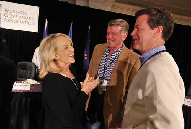 Governor of Arizona Jan Brewer, left, talks with fellow Governors Sam Brownback of Kansas, right, and Idaho's Butch Otter, during the annual Western Governors' Association Meeting, at the Broadmoor Hotel in Colorado Springs, Tuesday, June 10, 2014. Ten governors from western states attended the second day of the conference Tuesday, discussing common regional issues. (AP Photo/Brennan Linsley)