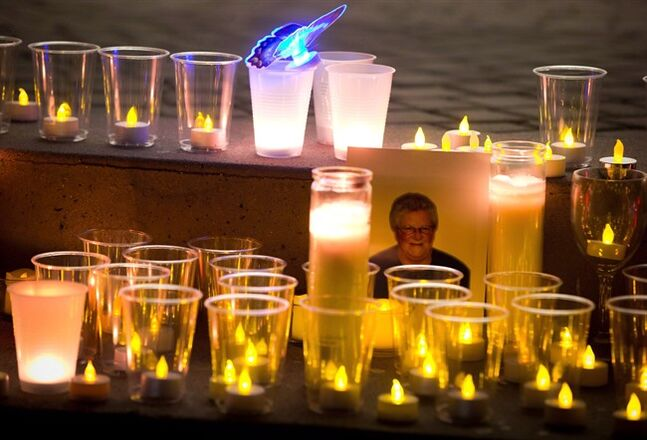 A photograph of the late Julie Paskall is surrounded by candles during a vigil in Surrey, B.C., on Saturday January 18, 2014. Homicide investigators have announced an arrest connected to the December 2013 murder of a 53-year-old hockey mom, a crime that shocked Surrey, B.C., and led many to question the city's safety. THE CANADIAN PRESS/Darryl Dyck
