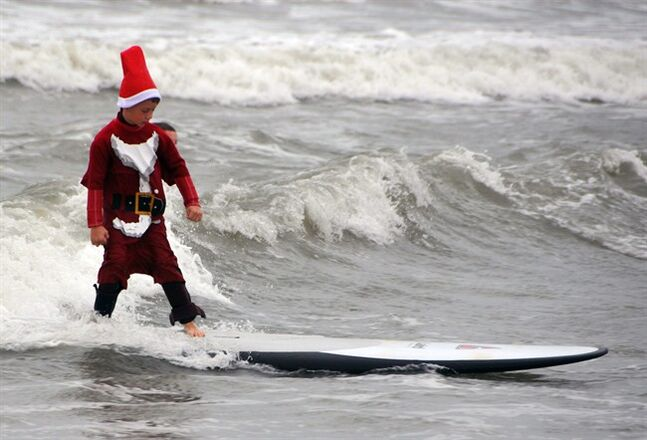 In this Tuesday, Dec. 24, 2013 photo, a young surfing Santa Claus hits the waves during the fourth annual