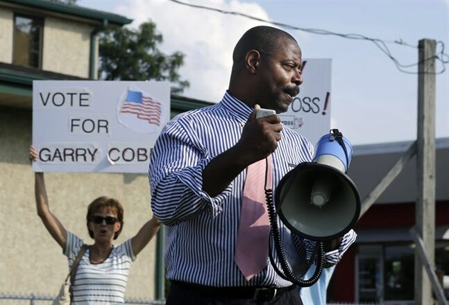 In this photo taken on Monday, Aug. 4, 2014, former Philadelphia Eagles NFL football player Garry Cobb, a Republican Congressional candidate in New Jersey's 1st Congressional District, uses a bull horn to address a gathering in Cherry Hill, N.J. (AP Photo/Mel Evans)