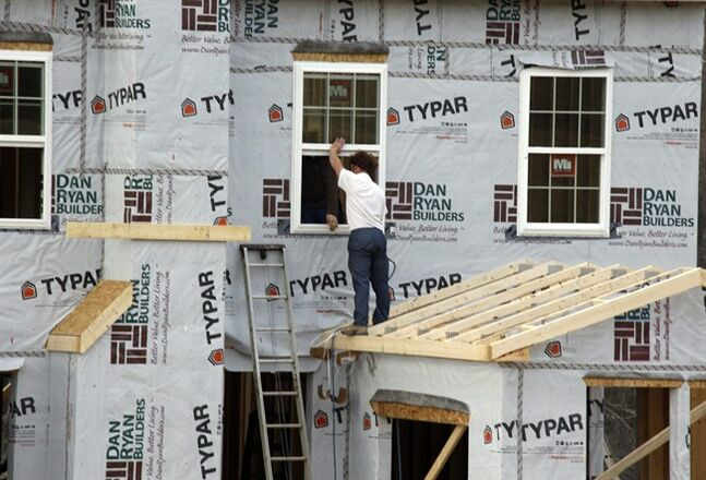 In this photo made on Friday, March 28, 2014, workers continue construction on a housing plan in Zelienople, Pa. The Commerce Department reports on U.S. home construction in May on Tuesday, June 17, 2014. (AP Photo/Keith Srakocic, File)