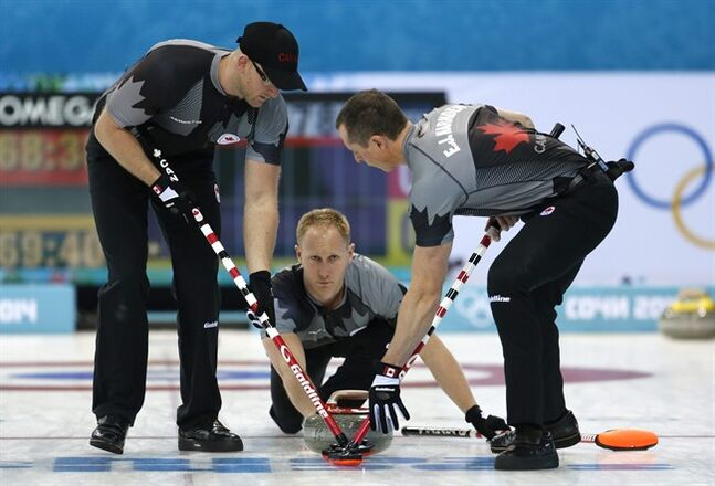 Canada's skip Brad Jacobs, center, delivers the rock to his sweepers Brian Harndin, left, and E. J. Harnden during men's curling competition against Sweden the 2014 Winter Olympics, Tuesday, Feb. 11, 2014, in Sochi, Russia. (AP Photo/Robert F. Bukaty)