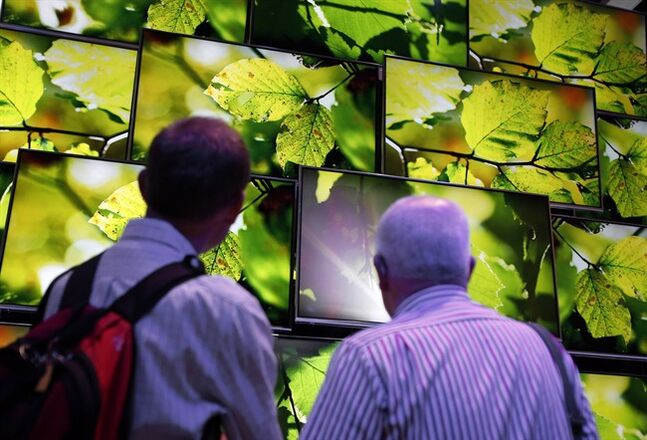 Visitors look at Panasonic Ultra HD TV screens in Berlin, Germany, Sept. 6, 2013.