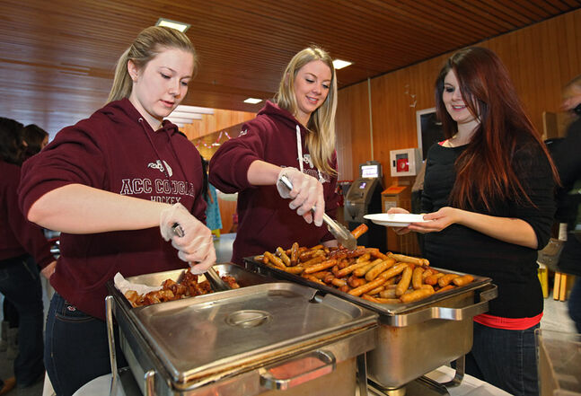 Shayna Fluker and Chantalle Crepeele with the ACC Cougars hockey team serve up bacon and sausage to students during a pancake breakfast party hosted by ACC in the Victoria Avenue East cafeteria on Wednesday morning. Early risers enjoyed breakfast while cheering on the Canadian women's hockey team as they took on Team USA at the Olympics.