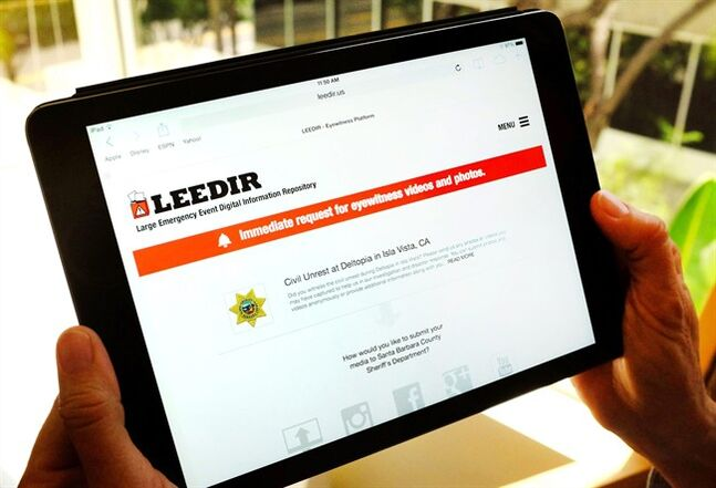 This photo taken Thursday, April 24, 2014 in Los Angles, shows a tablet computer displaying a web site for LEEDIR or the Large Emergency Event Digital Information Repository that aims to make use of a document-everything culture evident on Instagram, Facebook and other social media to benefit law enforcement nationwide. In the days after the Boston Marathon bombings, authorities were overwhelmed with video and pictures after calling on a public eager to help provide investigators with potential evidence. Los Angeles sheriff's Cmdr. Scott Edson approached two companies with a novel idea, a cloud-based repository for crowd-sourced videos and photos that could be flipped on in an emergency. (AP Photo/Richard Vogel)