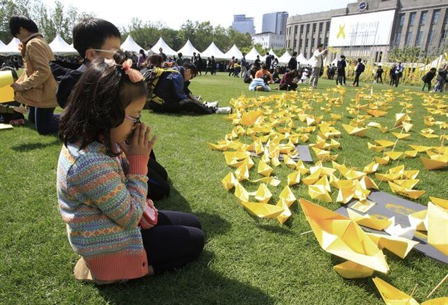 A girl prays in front of paper ships bearing messages for the victims of the sunken ferry Sewol at a group memorial altar in Seoul, South Korea, Monday, May 5, 2014. More than 300 people are dead or missing in the water off the southern coast in the disaster that caused widespread grief, anger and shame. (AP Photo/Ahn Young-joon)