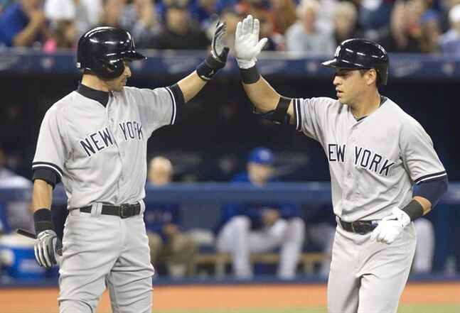 New York Yankees' Jacoby Ellsbury congratulated by teammate Ichiro Suzuki after hitting a two run home run against the Toronto Blue Jays during seventh inning AL baseball game action in Toronto Friday August 29, 2014. THE CANADIAN PRESS/Fred Thornhill