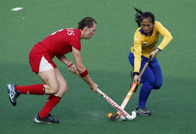 Canada's Kate Gillis, left and Malaysia's Norbaini Hashim fight for the ball during their women's field hockey match in the Commonwealth Games at the Major Dhyan Chand National Stadium in New Delhi, India, on Oct 4, 2010. Kate Gillis says it was difficult to block out the noise. The energetic 24-year-old is the captain and inspirational leader of Canada's women's field hockey team at the Commonwealth Games. She's also the daughter of former Vancouver Canucks president and general manager Mike Gillis, who was fired in April after the team missed the playoffs for the first time in six years. THE CANADIAN PRESS/AP, Eranga Jayawardena