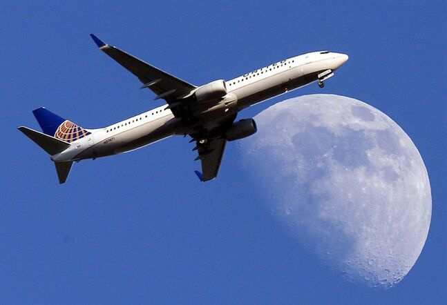 A United Airlines jet approaches LAX as it passes in front of a Waxing Gibbous moon on July 17, 2013. THE CANADIAN PRESS/AP, Nick Ut