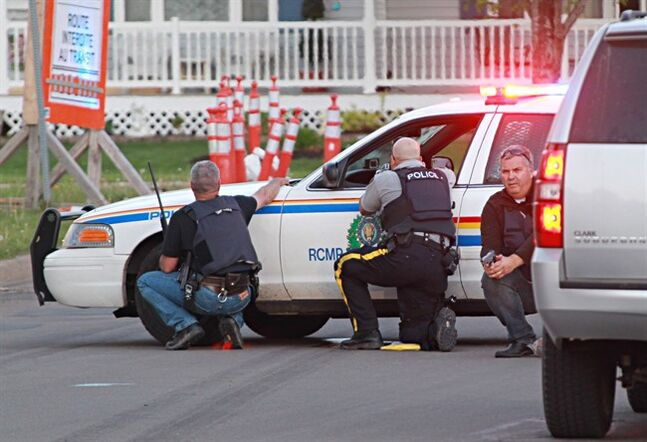 Police officers take cover behind their vehicles in Moncton, N.B. on Wednesday June 3, 2014. The RCMP says three of its officers were killed in Moncton, N.B., by a man armed with guns and two other officers were injured as the Mounties conducted a manhunt across the city's north end on Wednesday night for the shooter. THE CANADIAN PRESS/Moncton Times & Transcript-Ron Ward