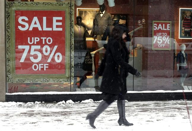 In this Jan 2, 2014 photo, a pedestrian passes by sale signs on a store front window in Chicago. The Conference Board releases the Consumer Confidence Index for January, on Tuesday, Jan. 28, 2014. (AP Photo/Kiichiro Sato)