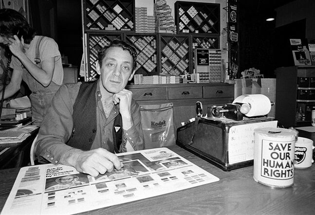 "FILE - This June 28, 1977 file photo shows gay activist and political leader Harvey Milk in his camera store in San Francisco. A concert piece about Harvey Milk by Tony Award-nominee Andrew Lippa that had its world premiere last summer in San Francisco is coming to New York and it's bringing Kristin Chenoweth along with it. Producers said Thursday that ""I Am Harvey Milk"" will have its New York premiere on Oct. 6 at Lincoln Center's Avery Fisher Hall as part of a one-night-only benefit to help provide arts education for at-risk youth. The director is Noah Himmelstein. (AP Photo, File)"