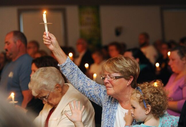 Lillian LaRose, Heuvelton, holds up a candle on Thursday, Aug. 14, 2014 during a candlelight vigil at the Cornerstone Wesleyan Church in Heuvelton for Fannie Miller, 12, and her sister Delila Miller, 6, who were still missing after being abducted Wednesday night at a farm stand near their home. (AP Photo/The Watertown Daily Times, Jason Hunter)
