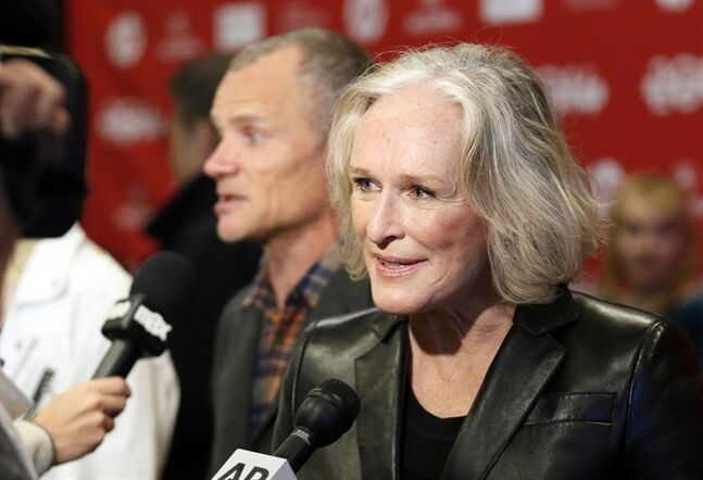 Cast member Glenn Close speaks with reporters as fellow cast member Flea, rear, of the Red Hot Chili Peppers, is also interviewed at the premiere of the film