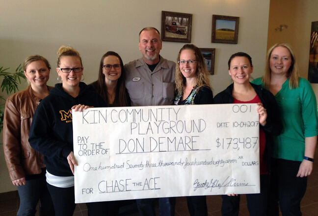 An oversized cheque for Don DeMare, the winner of Pilot Mound's Chase the Ace raffle, gathers with representatives of the Kin Community Playground committee members on April 10. He and his girlfriend, Ferne Morgan, are splitting the winnings.