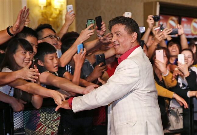 U.S. actor Sylvester Stallone shakes hands with fans at the red carpet for the Macau premiere of his movie