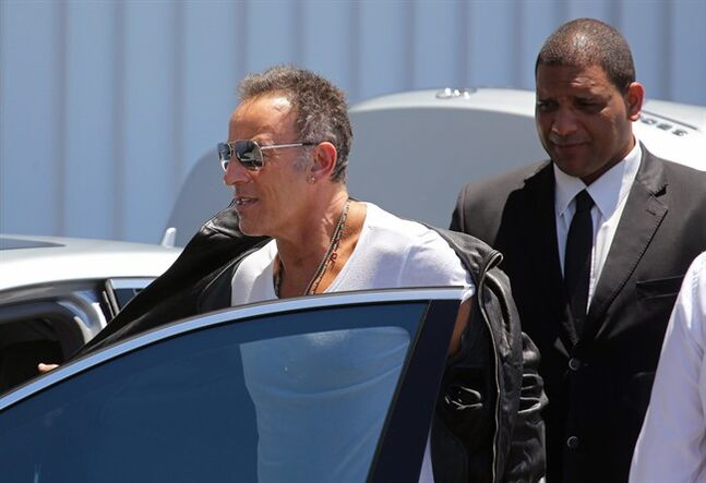 American performer Bruce Springsteen, center, removes his jacket as he arrives at the airport in Cape Town, South Africa, Friday, Jan. 24, 2014. Bruce Springsteen begin his first South African tour on Sunday, Jan. 26, in Cape Town. (AP Photo/Schalk van Zuydam)