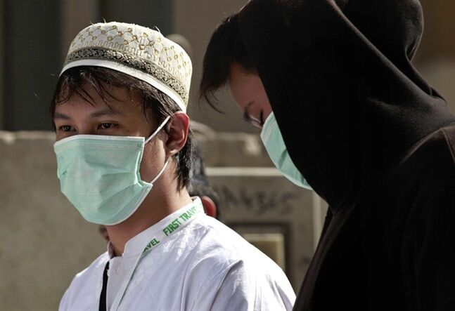 FILE -- In this Tuesday May, 13, 2014 file photo, Muslim pilgrims wear surgical masks to help prevent infection from a respiratory virus known as the Middle East Respiratory Syndrome (MERS) in the holy city of Mecca, Saudi Arabia. Saudi, which is grappling to contain the spread of a frequently deadly respiratory virus, announced Tuesday, June 3, 2014 that a review of the illness led authorities to sharply revise upward the number of confirmed infections and deaths from the disease. A report by the official Saudi Press Agency said authorities have registered a total of 688 confirmed infections and 282 deaths as a result of MERS since the virus was first identified in 2012. (AP Photo/Hasan Jamali, File)