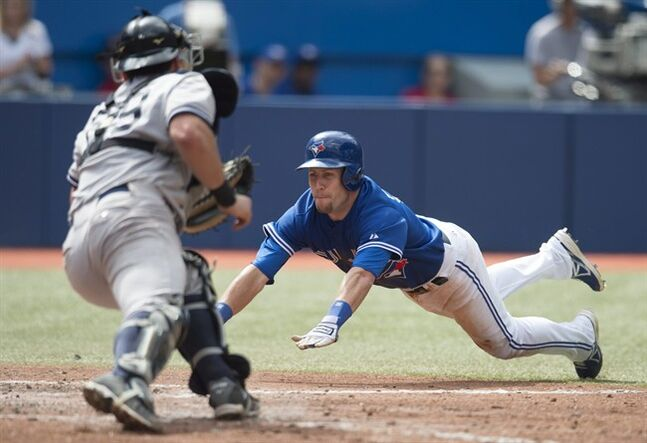 Toronto Blue Jays' Steve Tolleson, right, slides safely past New York Yankees catcher Francisco Cervelli to score on a Munenori Kawasaki RBI-single in the seventh inning of a baseball game in Toronto, Sunday, Aug. 31, 2014. (AP Photo/The Canadian Press, Darren Calabrese)