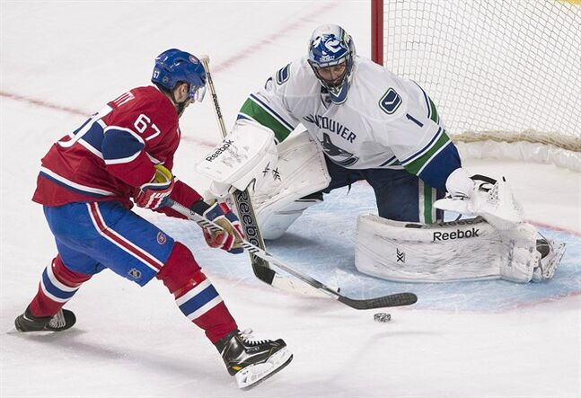 Vancouver Canucks' goaltender Roberto Luongo stops a penalty shot against Montreal Canadiens' Max Pacioretty during second period NHL hockey action in Montreal, Thursday, February 6, 2014. THE CANADIAN PRESS/Graham Hughes