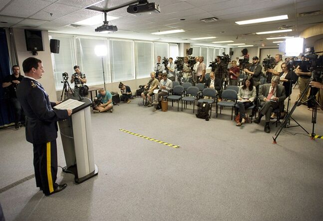 Journalists listen as RCMP Assistant Commissioner Gilles Michaud, Commanding Officer of the RCMP'��s National Division, announces criminal charges against Senator Mike Duffy in Ottawa on Thursday, July 17, 2014. THE CANADIAN PRESS/Justin Tang