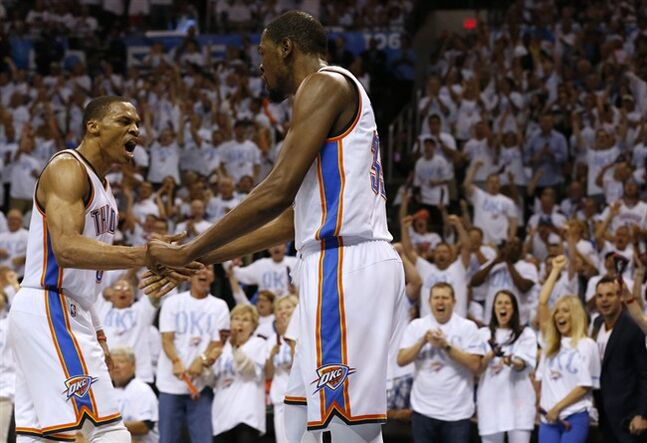 Oklahoma City Thunder's Russell Westbrook, left, and Kevin Durant (35) celebrate during the first half against the San Antonio Spurs in Game 6 of the Western Conference finals NBA basketball playoff series in Oklahoma City, Saturday, May 31, 2014. (AP Photo/Sue Ogrocki)