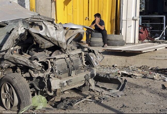 A man sits in front of his shop that was damaged in a Saturday car bomb attack near a Kebab restaurant, in the mainly Shiite Habibiya neighborhood of Baghdad, Iraq, Sunday, May 11, 2014. A series of bombings on Saturday in Iraq killed and wounded scores of people, a day after army shelling killed many civilians and gunmen in the militant-held city of Fallujah, authorities said. (AP Photo/Karim Kadim)