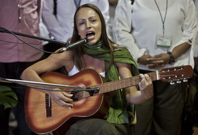FILE - In this March 26, 2014 file photo, Dutch-born guerrilla Tanja Nijmeijer, of the Revolutionary Armed Forces of Colombia, or FARC, sings a tribute to FARC founder Manuel Marulanda, on the sixth anniversary of his death, in Havana, Cuba. Colombia's largest rebel group is trying to rally support for peace talks with a new rap video. Nijmeijer features prominently in the video, which exalts the FARC's role as a defender of Colombia's peasants. (AP Photo/Franklin Reyes, File)
