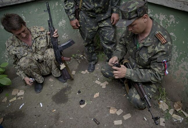 Pro-Russian rebels reload weapons during clashes with Ukrainian troops on the outskirts of Luhansk, Ukraine, Monday, June 2, 2014. Hundreds of pro-Russia insurgents attacked a border guard base in eastern Ukraine on Monday, with some firing rocket-propelled grenades from the roof of a nearby residential building. At least five rebels were killed when the guards returned fire, a spokesman for the border guard service said.(AP Photo/Vadim Ghirda)