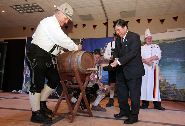 Manfred Wicht with the German Society of Westman steadies the keg as Manitoba Lt.-Gov. Philip S. Lee taps the keg to mark the official opening of the German pavilion on the first night of the Lieutenant Governor's Winter Festival on Thursday.