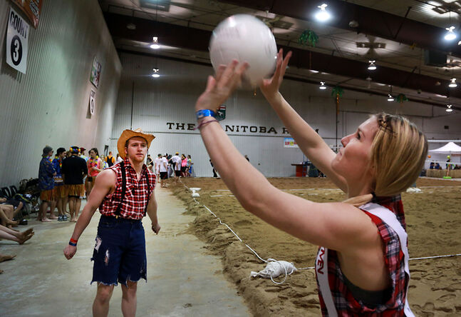 Jennifer Diboll sets the ball to teammate Dillon Grant as the pair warm up for their match on the opening day of the Sun of a Beach indoor volleyball tournament on Friday afternoon.