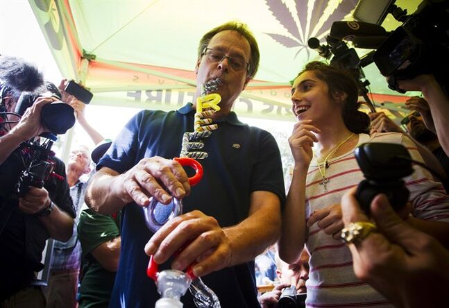 Marijuana activist Marc Emery smokes from a bong with the words 'Freedom' on it during his return party in downtown Vancouver, B.C., on Sunday, August 17, 2014. THE CANADIAN PRESS/Ben Nelms
