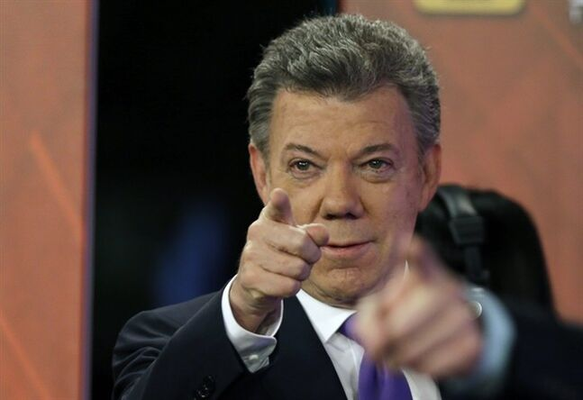 Colombian President Juan Manuel Santos who is seeking a second four-year term as candidate for the Social Party of National Unity, gestures during a televised presidential debate in Bogota, Colombia, Monday, June 9, 2014. Colombia will hold presidential runoff elections on June 15. (AP Photo/Fernando Vergara)