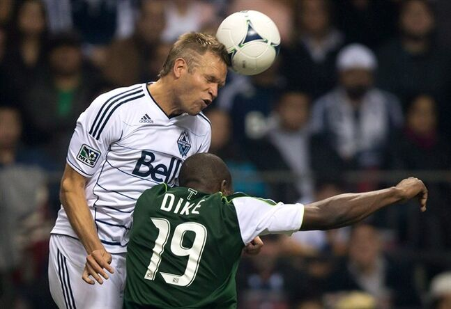 Vancouver Whitecaps' Jay DeMerit, left, heads the ball as Portland Timbers' Bright Dike challenges during the second half of an MLS soccer game in Vancouver, B.C., on Sunday October 21, 2012. DeMerit, the first player signed by the expansion Whitecaps in 2010 and the first captain of the Major League Soccer team, officially announced his retirement Thursday, saying he was proud of his career and thanking all those that supported him.THE CANADIAN PRESS/Darryl Dyck