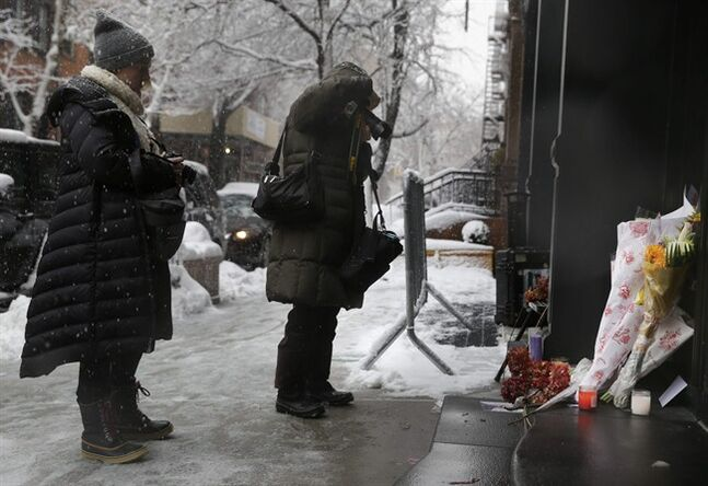 People stop to look and take pictures of a makeshift memorial in front of the building where the body of actor Philip Seymour Hoffman was found, Monday, Feb. 3, 2014, in New York. Hoffman, 46, was found dead Sunday in his apartment of a suspected drug overdose. (AP Photo/Seth Wenig)
