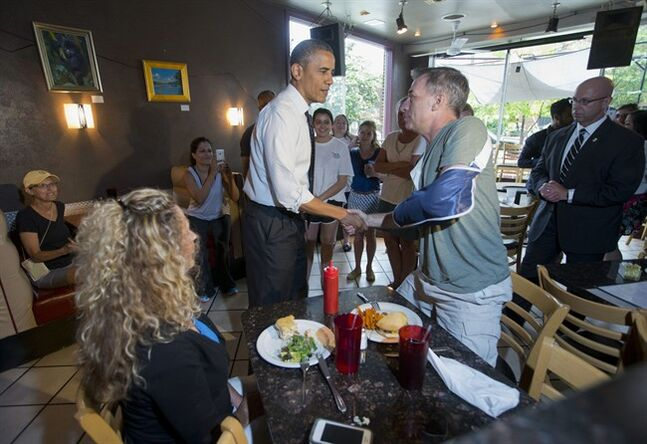 President Barack Obama greets patrons after having lunch during his unannounced visit to FireFlies restaurant in the Del Ray neighborhood of Alexandria, Va., Tuesday, June 10, 2014. President Barack Obama Education Secretary Arne Duncan, went on a lunch outing to an Alexandria, Virginia, neighborhood known for its good restaurants. The White House said Obama went to FireFlies Restaurant on Tuesday because the owner wrote him earlier this year and asked him to come try the best burger around. (AP Photo/Pablo Martinez Monsivais)