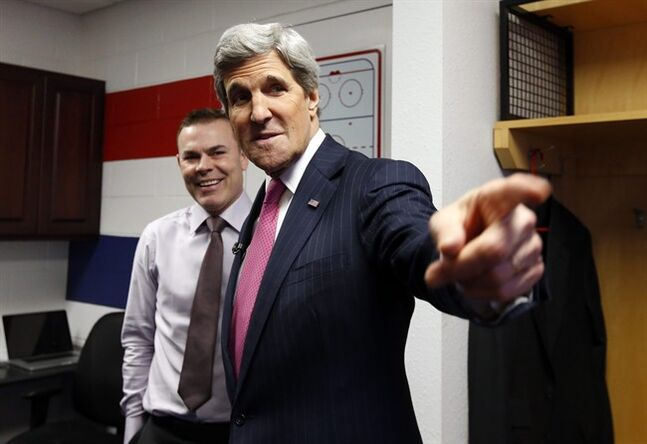 Secretary of State John Kerry, right, talks with Washington Capitals head coach Adam Oates in the locker room before their game with the Winnipeg Jets, Thursday, Feb. 6, 2014, in Washington. Kerry was greeting players that have been selected for their country's Olympic hockey team. (AP Photo/Alex Brandon, Pool)