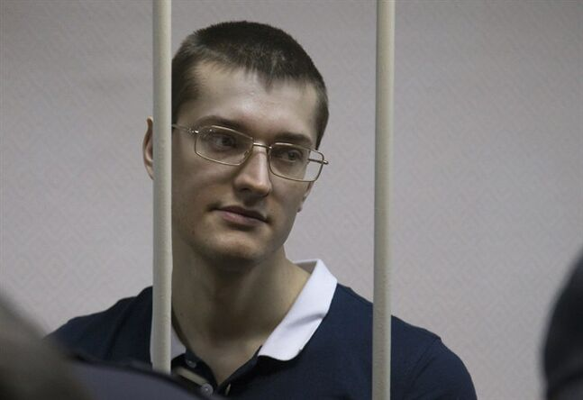 ADDS NAME OF DEFENDANT Opposition activist Yaroslav Belousov stands behind bars in a cage at a court room in Moscow, Russia, Monday, Feb. 24, 2014, where hearings started against opposition activists detained on May 6, 2012 during a rally at Bolotnaya Square. A Moscow judge on Friday, Feb. 21, 2014, convicted eight anti-government protesters of rioting during a 2012 protest against Vladimir Putin, following a trial seen as part of the Kremlin's efforts to stifle dissent. (AP Photo/Alexander Zemlianichenko)