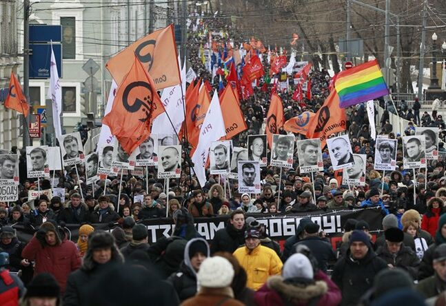 Opposition demonstrators carry posters of imprisoned protesters during a protest rally in Moscow, Russia, Sunday, Feb. 2, 2014. Several thousand Russian opposition supporters gathered for a protest on Sunday, venting anger against the Kremlin and demanding the release of political prisoners. (AP Photo/Alexander Zemlianichenko)