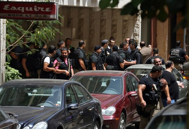 Lebanese police intelligence gather outside a hotel after security forces raided there in Beirut's Hamra district, Lebanon, Friday, June 20, 2014. Security forces raided the hotel over suspected