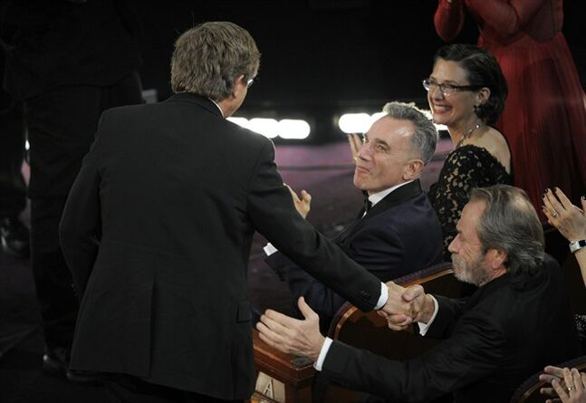 From right, Tommy Lee Jones and Daniel Day Lewis congratulate Rick Carter as Carter walks on stage to accept the award for best production design for