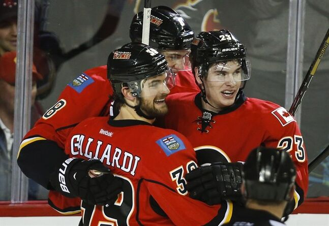 Calgary Flames' Sean Monahan, right, celebrates with teammates in Calgary, Thursday, Jan. 30, 2014. THE CANADIAN PRESS/Jeff McIntosh